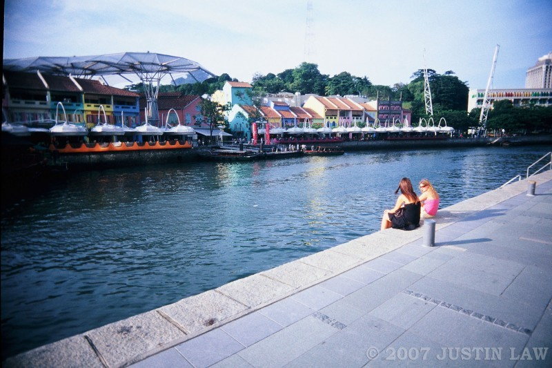 two ladies sitting by the river near clarke quay