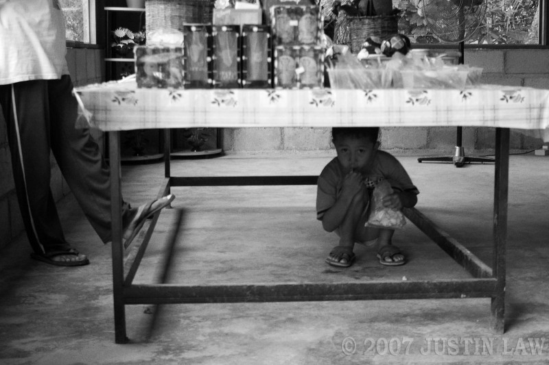village boy squatting under table