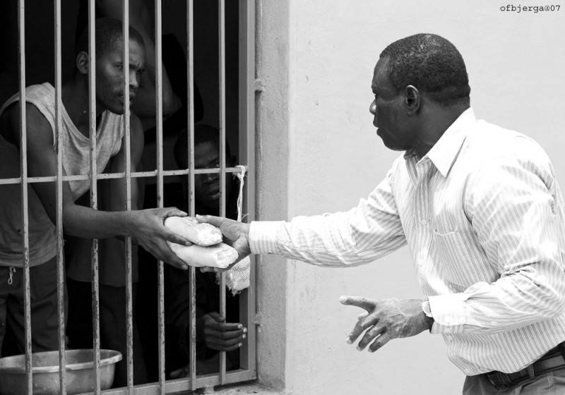 Pastor giving bread to prisoner