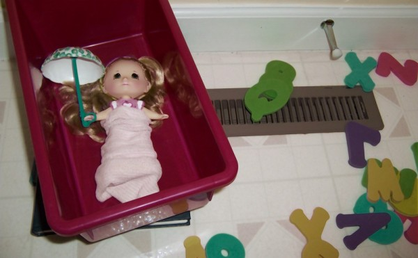 The doll sleeps in her bin