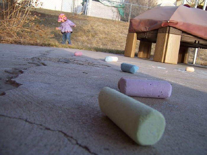 A three year old takes a shot of chalk and sister