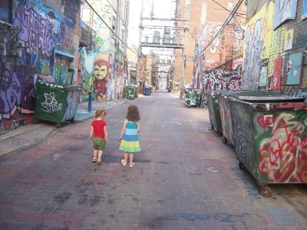 Two girls stroll down art alley
