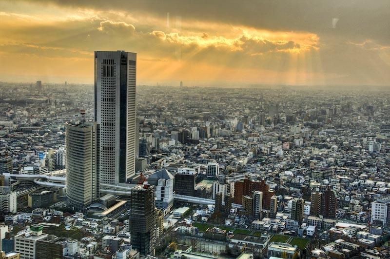 Tokyo's skyline, sun behind clouds, Japan