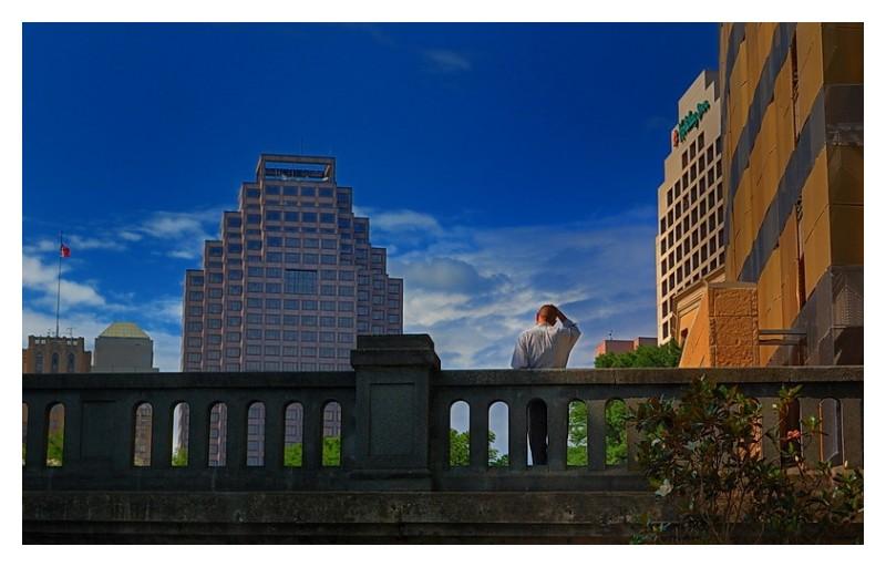 Man on bridge over San Antonio Riverwalk