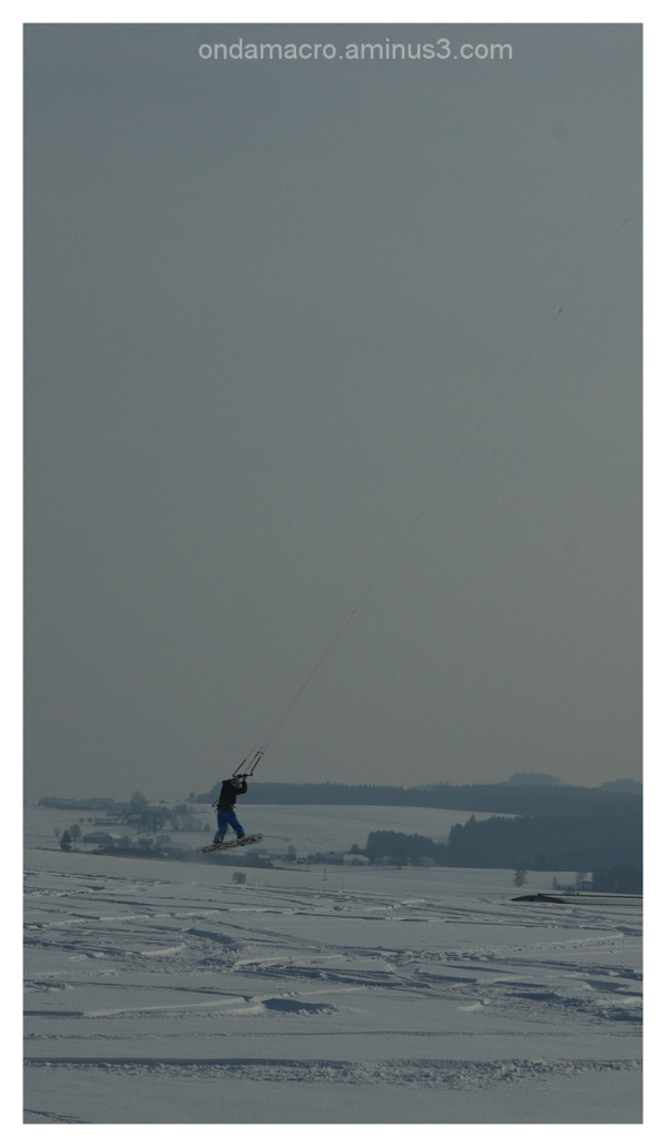 Man jumping on snow with kite