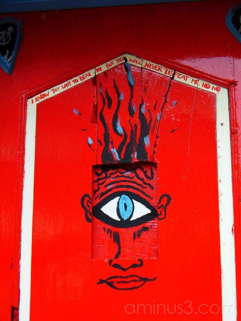 Red door with painted eye and slogan