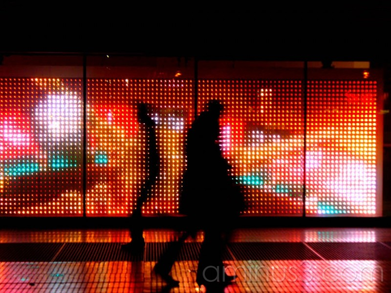 Silhoutes of pedestrians in front of bright lights