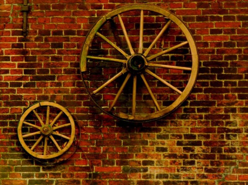 Old wagon wheels on brick wall