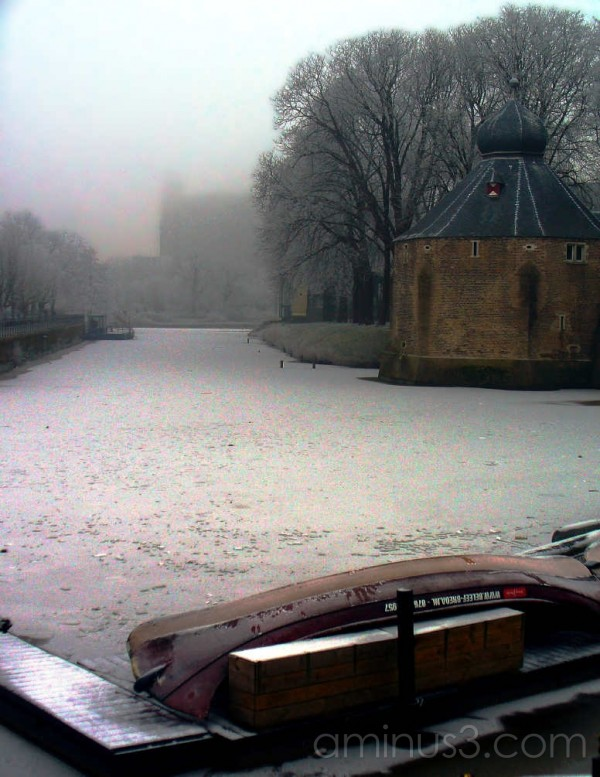 Upturned pleasure boat in front of frozen canal