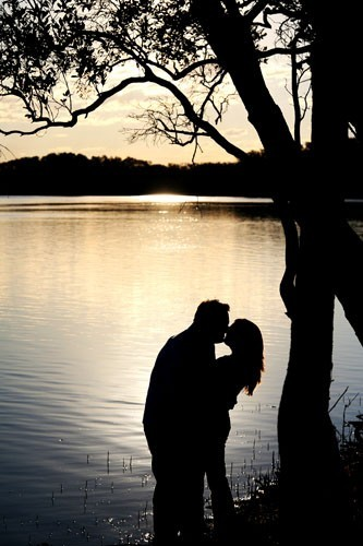 Silhoette of couple kissing on lake edge at sunset