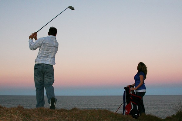 golfer teeing off on cliff edge