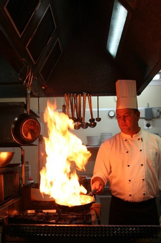 Chef in kitchen with wok flaming