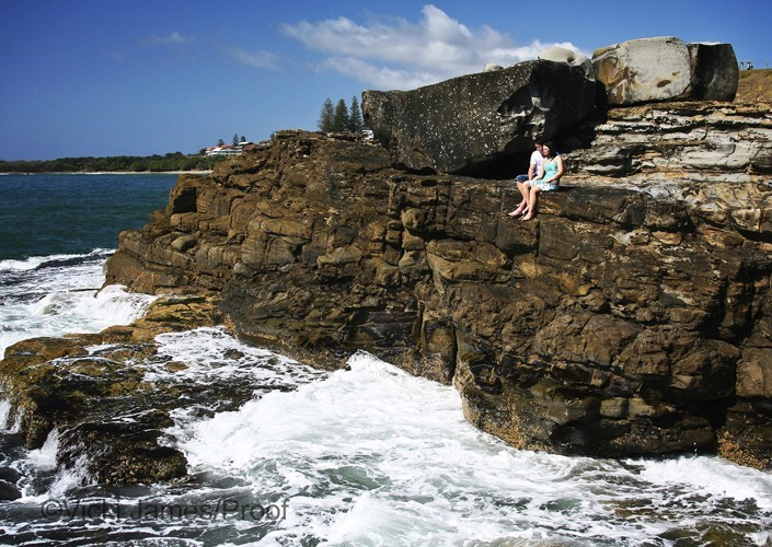 Couple sitting on edge of cliff looking into water