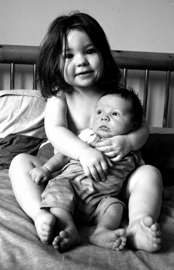 Big sister cuddles little brother