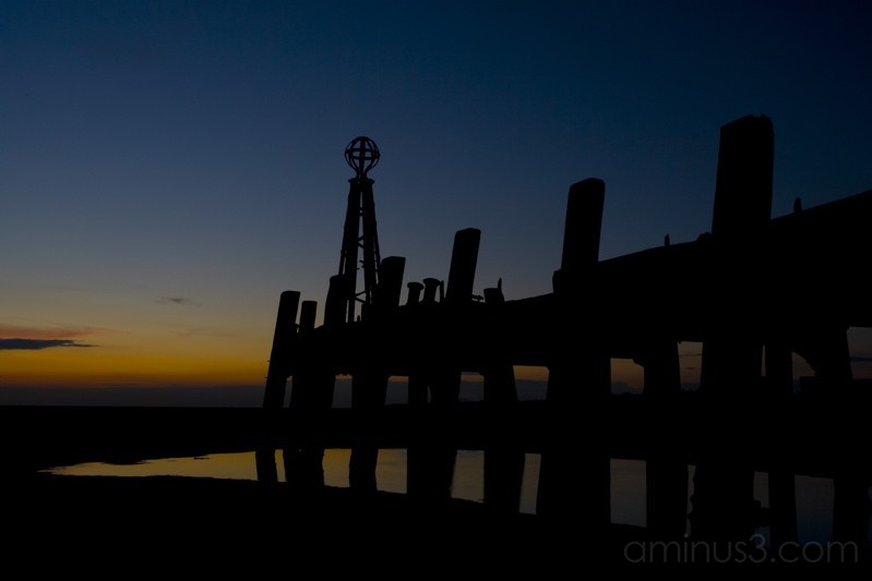 The sun sets in the west over the pier