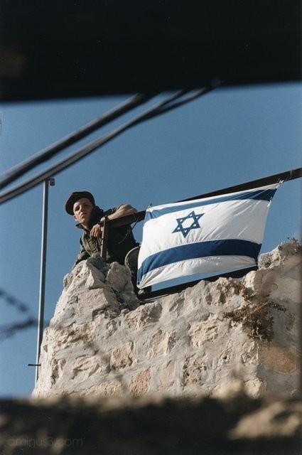Israeli solder stands watch, flag of Israel Hebron