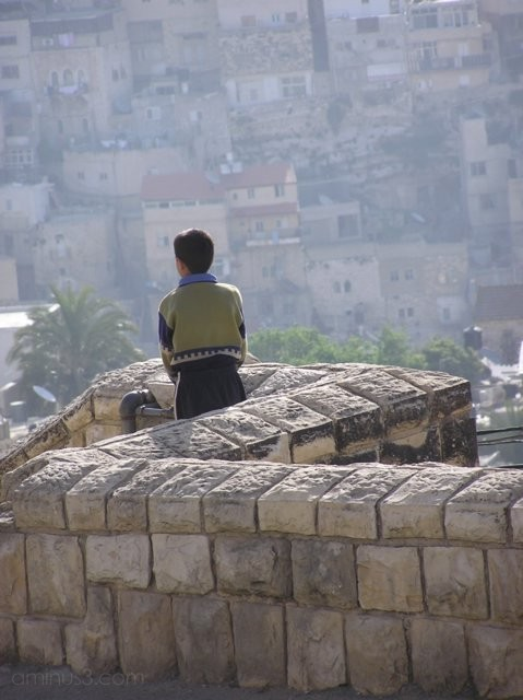 Young boy looks out at the houses of East Jerusale