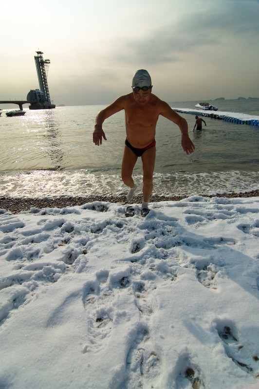 Man stepping out of the sea onto snowy beach.