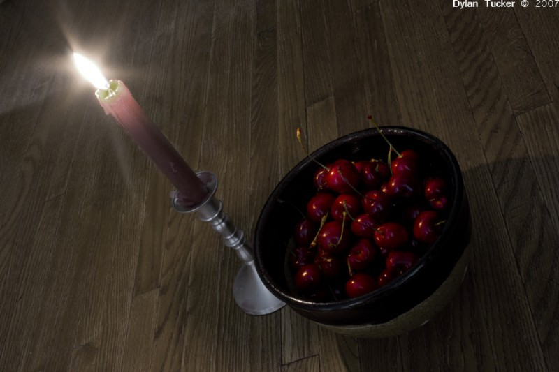 Cherries in a bowl under candle light