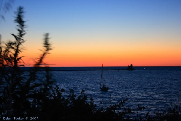 sailboat and lighthouse at sunset