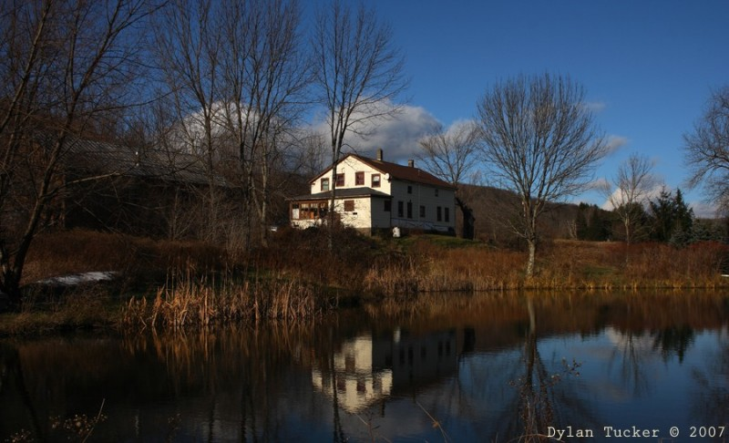 reflection of a farm house in a pond