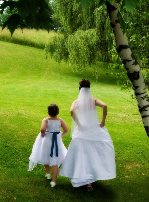 Bride and Flower Girl walking in the Grass