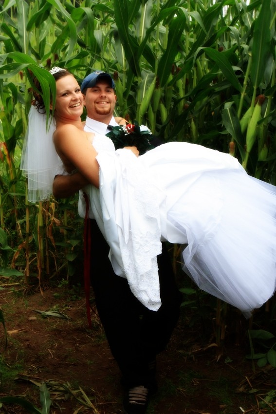 Groom carrying the Bride through a corn field.