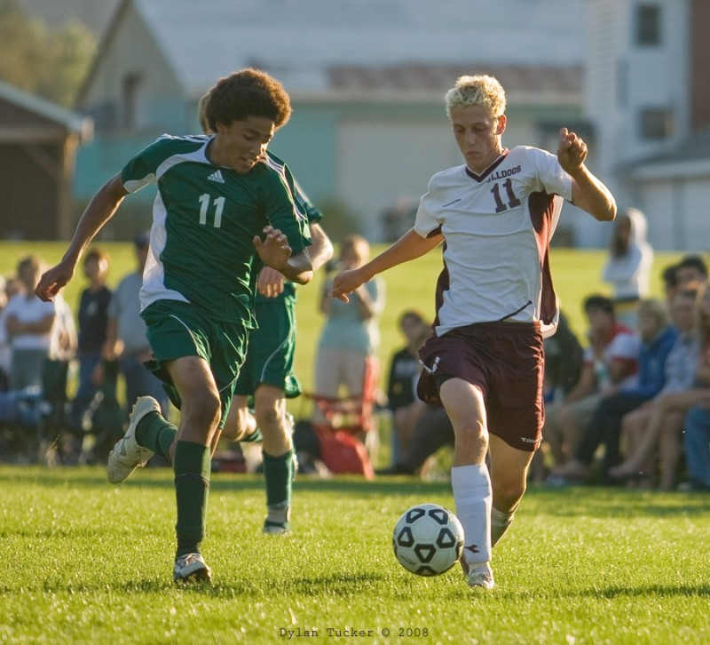 two players running for a loose ball in soccer
