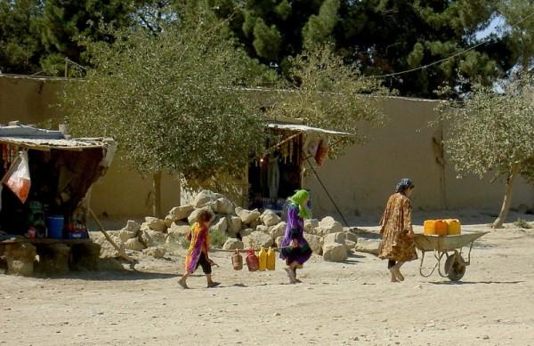 Afghan girls carrying water