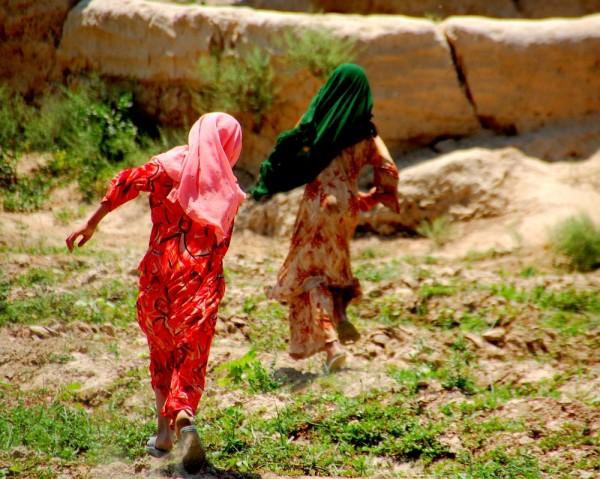 afghan girls running through the field