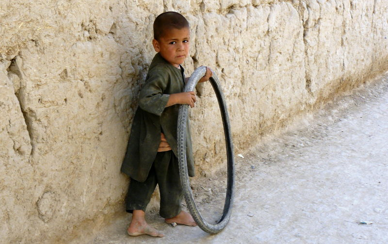 Afghan Turkmen boy with a bycicle tire
