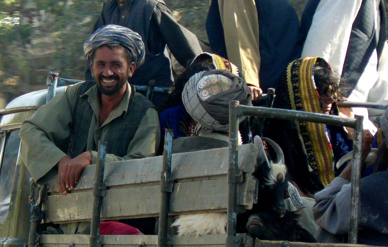 afghan man smiling happy women in bright clothes