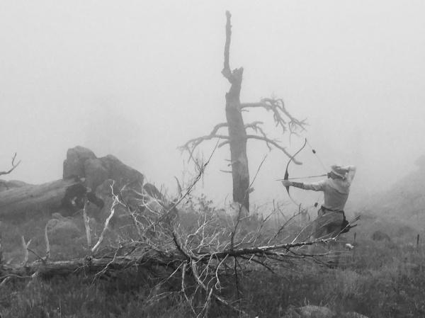 Man shooting arrows in a foggy morning