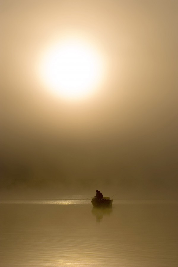 Fisherman slowly being engulfed by the morning fog
