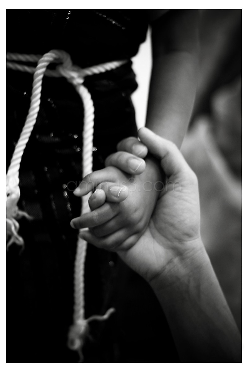 An adult holding a child's hand