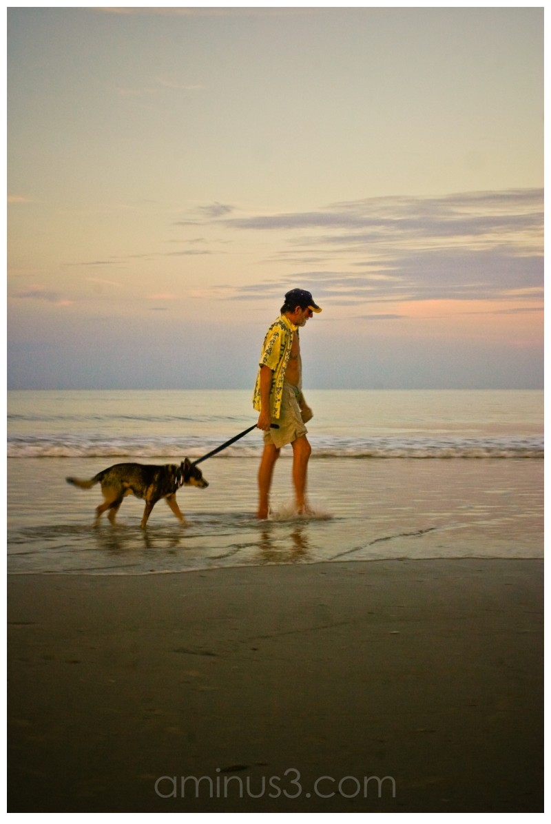 a man walking his dog at the end of the day