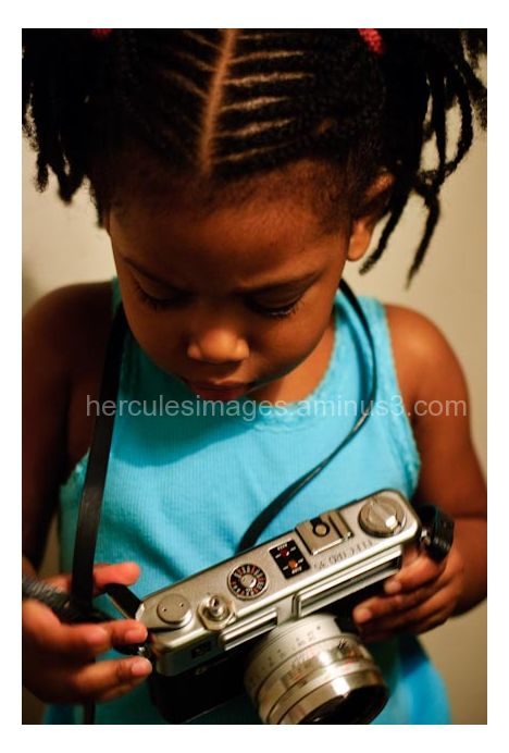A child holding a classic camera