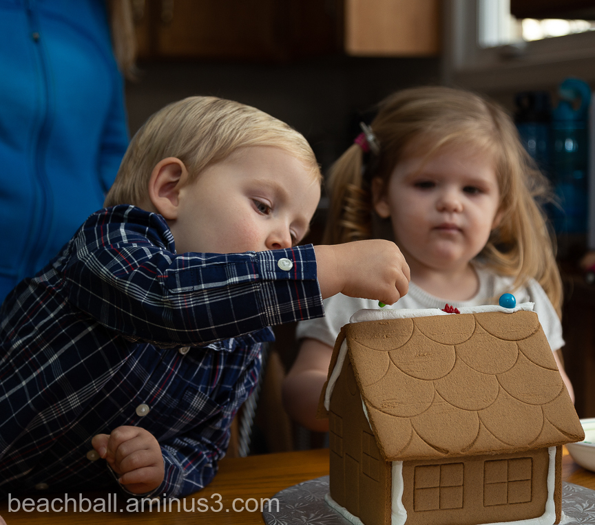 Little boy decorating a gingerbread house