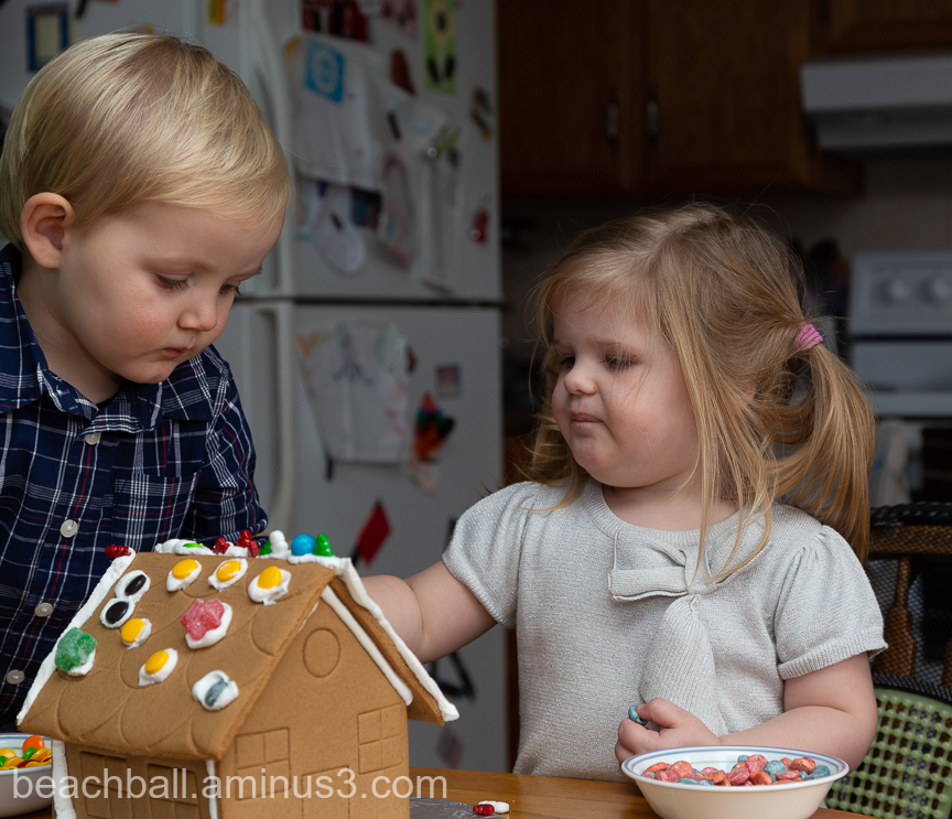 Little boy and girl decorating a gingerbread house