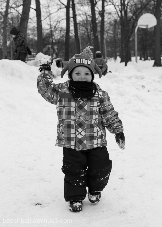 little boy throwing a snow ball