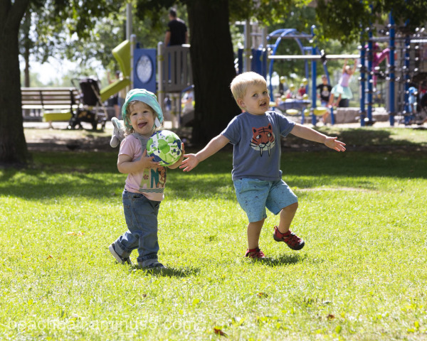 Two little boys play in a park