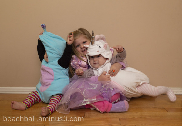 three girls posing in halloween costumes.