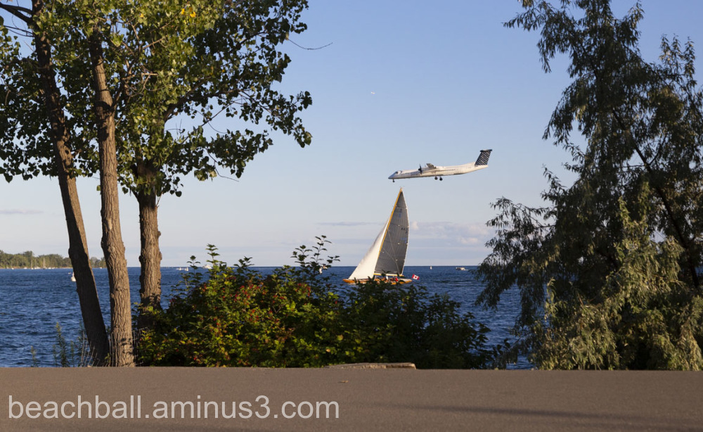 Plane landing over a sailboat