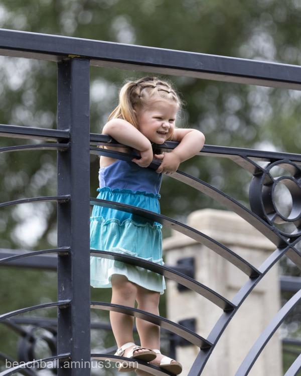 Little girl standing on a rail.