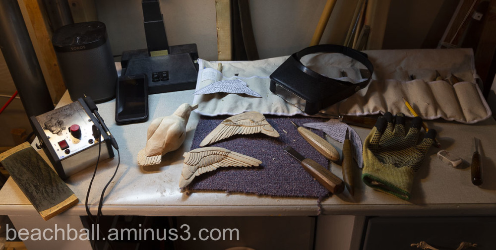 A wood carving desk with tools and unfinished bird