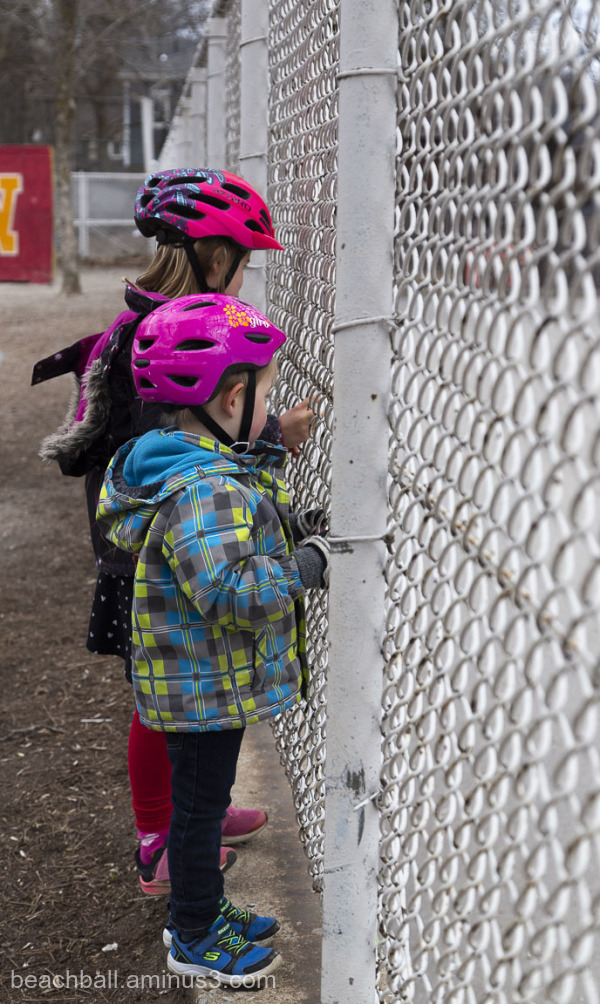 two children looking through a fence