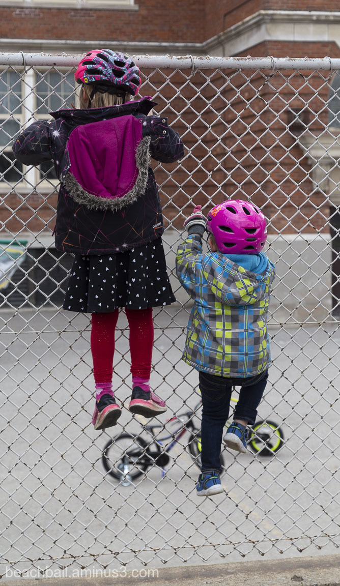 Two children climb a fence
