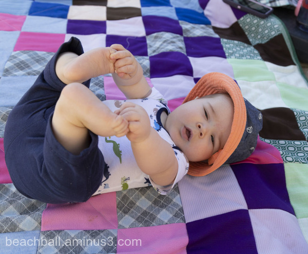Little boy grabbing his toes.