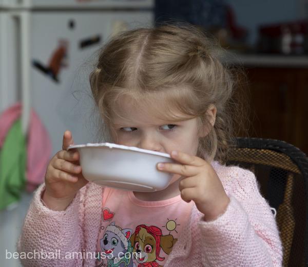 Little girl drinking milk from her bowl