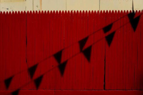 Flag shadows on a fence